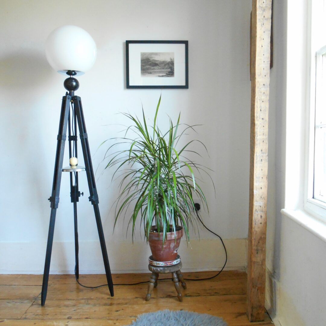 Tripod floor lamp with unique monochrome features and a glass globe shade by Fiona Bradshaw Designs